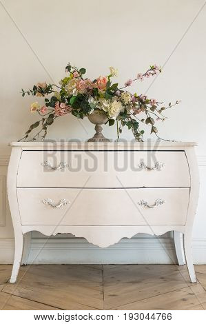 Vintage commode with the flowers in luxury clean bright white interior