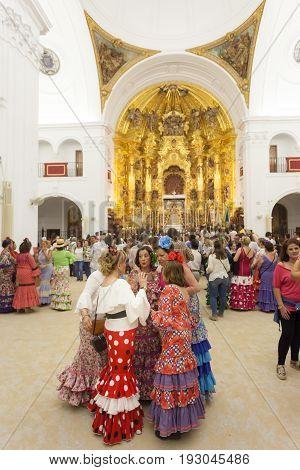 El Rocio Spain - June 1 2017: Group of female pilgrims in traditional spanish flamenco dress in the hermitage of El Rocio during the Romeria 2017. Andalusia Spain