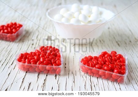 Red cinnamon hearts displayed in heart shaped containers.