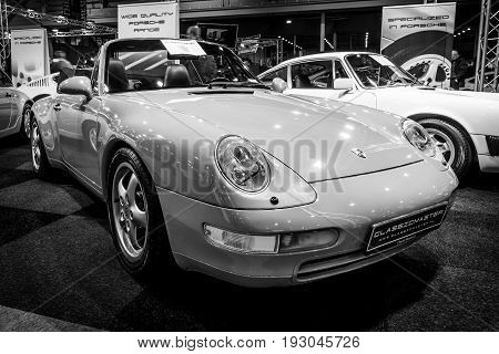 MAASTRICHT NETHERLANDS - JANUARY 15 2016: Sports car Porsche 911 Carrera (993) Cabriolet 1995. Black and white. International Exhibition InterClassics & Topmobiel 2016