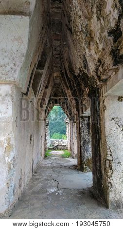 Unusual triangular perspective through stone archway of archeological ruins, Palenque, Mexico.