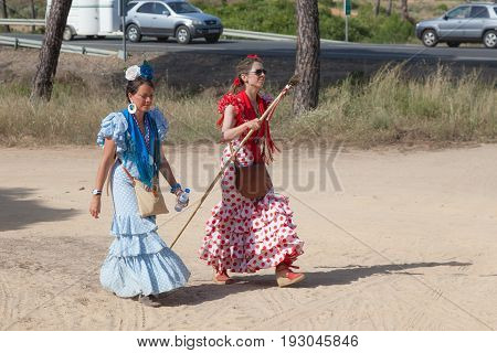 El Rocio Spain - June 1 2017: Women with traditional spanish flamenco dress on the road to El Rocio during the Romeria 2017. Province of Huelva Almonte Andalusia Spain