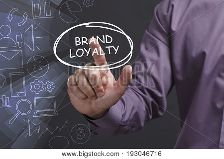 Business, Technology, Internet And Network Concept. Young Businessman Shows The Word: Brand Loyalty