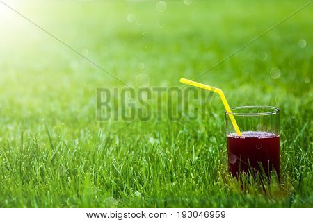 A glass of juice in the grass