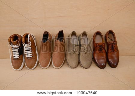 Fashion male row of shoes on wooden background