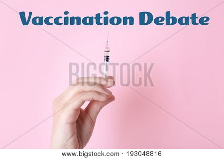 Vaccination debate concept. Doctor holding syringe with vaccine on color background