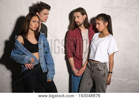 Picture of concentrated young hipsters loving couples standing over gray background.