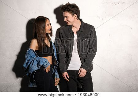 Image of smiling young hipster loving couple looking aside over gray background
