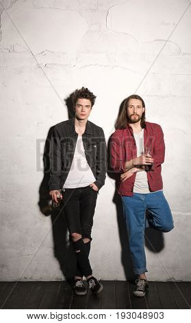 Picture of concentrated young hipsters friends standing over gray background drinking aerated sweet water.
