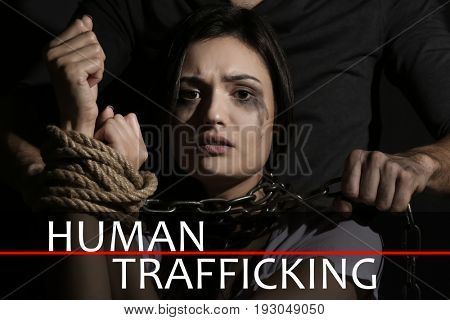 Concept of human trafficking. Young woman with tied hands subjected to violence