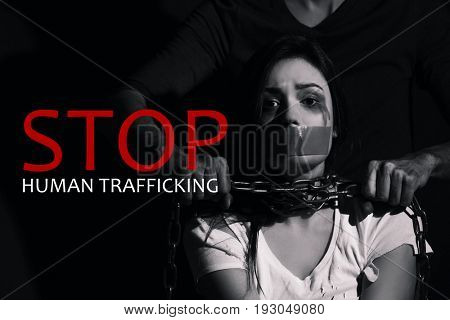 Text STOP HUMAN TRAFFICKING and young woman subjected to violence on black background
