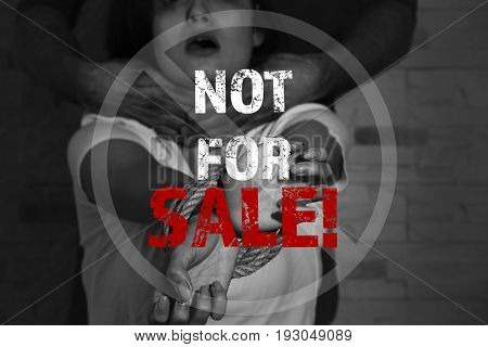 Concept of human trafficking. Text NOT FOR SALE and young woman with tied hands subjected to violence on background