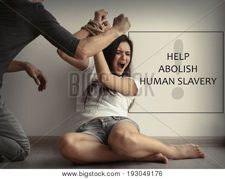 Young woman subjected to violence and text HELP ABOLISH HUMAN SLAVERY on background