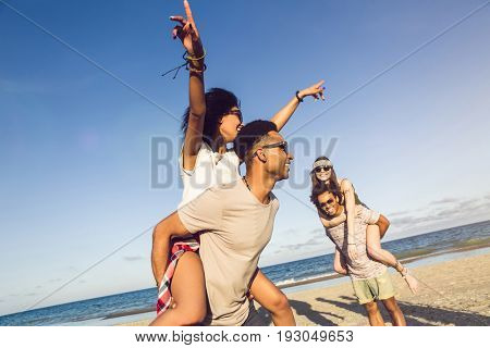 Two young men giving their girlfriends piggyback rides at the beach