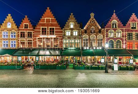 Market Square in Bruges Belgium evening landscape panorama with summery of restaurant and ancient architecture medieval town.