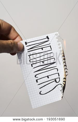 young man burning a piece of paper with the text influencers written in it