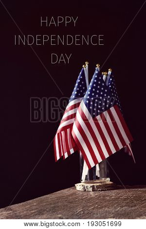 some american flags in a glass jar, on a rustic wooden surface and the text happy happy independence day on a black background