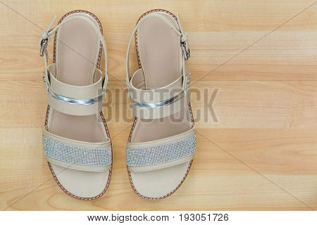Top view of classic flat sandal in beige with beautiful diamond like shimmer sparkling topped straps for ladies on wooden background