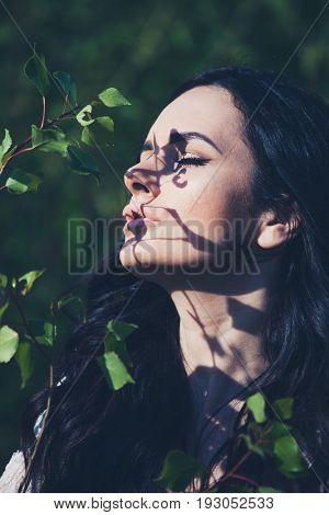 beautiful summer dark hair woman portrait in nature with green leaves light and shadow