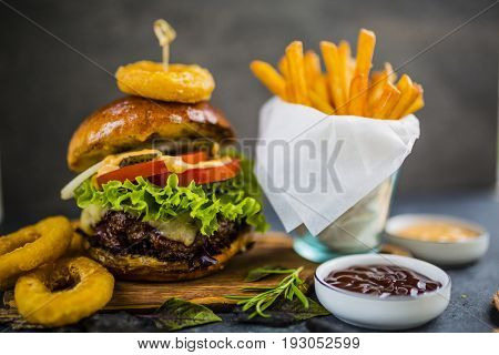 Tasty grilled glazed beef burger with lettuce and cheese served on wooden table with copyspace, blackboard in background.