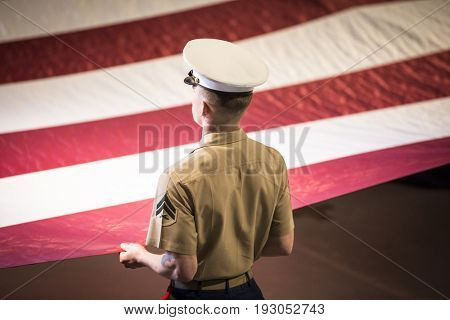 U.S. Marine Corps military service member holds a large American Flag during the Memorial Day Observance ceremony on the Intrepid Sea, Air & Space Museum, Fleet Week, NEW YORK MAY 29 2017.