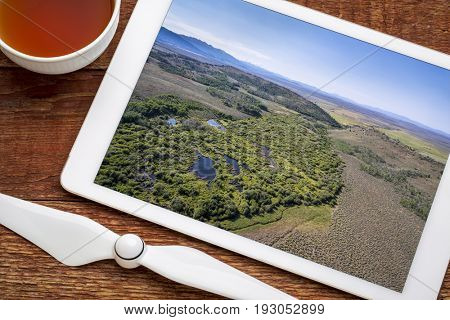 reviewing aerial pictures of a stream at foothills of Medicine Bow Mountains (North Park, Colorado) on a digital tablet with a cup of tea