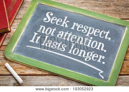 Seek respect, not attention. It last s longer. Motivational text on a slate blackboard with a white chalk and a stack of books.