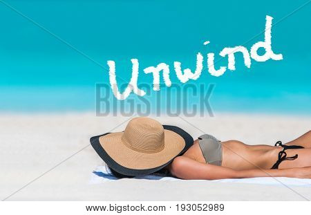 UNWIND word written on sky above beach travel bikini suntan woman sleeping relaxing covering face with hat doing siesta. UNWIND text in blue ocean copy space above. Summer and sun vacation holidays.