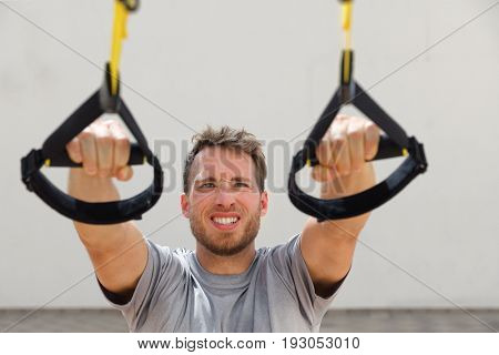 Suspension straps exercises man training arms workout at outdoor gym. Athlete holding suspended handles doing inclined pull-ups for back muscles.