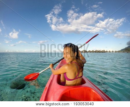 Kayak woman having fun kayaking at tropical beach resort in Tahiti vacation travel. Asian girl paddling in ocean water smiling. Action camera.