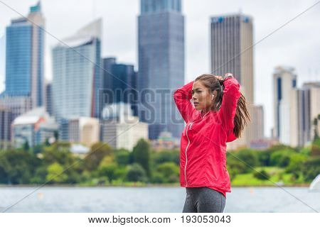 Running healthy lifestyle in Sydney city runner Asian woman preparing her hair to run morning exercise.