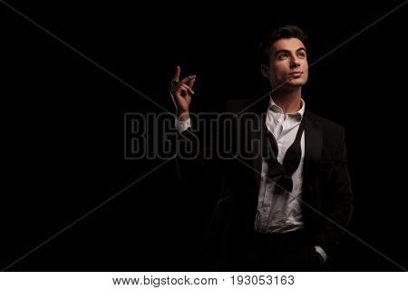 elegant man in tuxedo snapping his fingers and looks up on black background