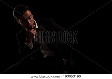 man in tuxedo wearing big ring in thinking on black background, while sitting on chair