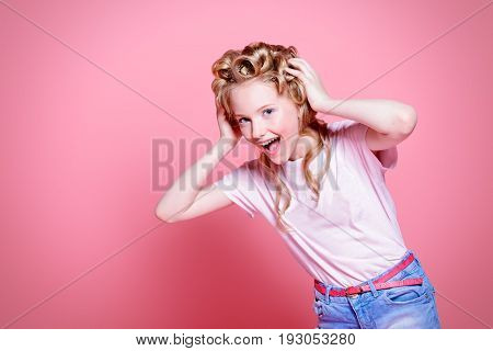 Portrait of a shouting pretty girl teenager with curlers in her blonde hair. Teen style, fashionable teen girl. Studio shot over pink background.