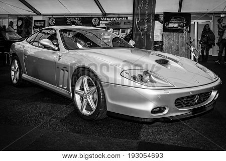 MAASTRICHT NETHERLANDS - JANUARY 15 2016: Grand tourer Ferrari 575M Maranello 2003. Black and white. The designer of the car body Lorenzo Ramaciotti at Pininfarina. Intern. Exhibition InterClassics & Topmobiel 2016