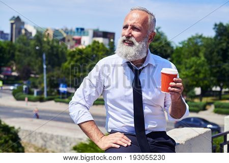 Bearded sir drinking coffee and enjoying panorama of city