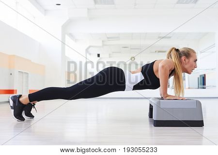 Side view of sporty strong female doing push up abdominals workout posture