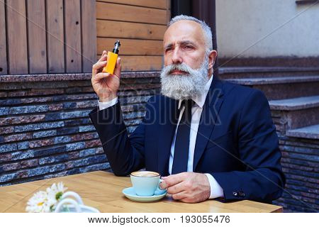 Mid shot of sir with grey beard drinking coffee while smoking electrocigarette