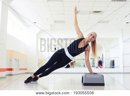Side view shot of fitness side push ups of sporty woman doing side push up at gym workout execises