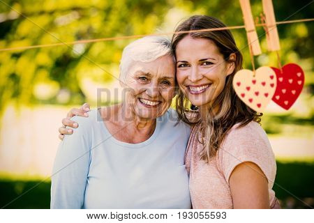 Hearts on line against happy mother and daughter standing at park
