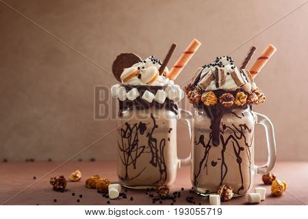Chocolate  milkshake with ice cream and with whipped cream, marshmallow, sweet popcorn, cookies, waffles, served in glass mason jar.