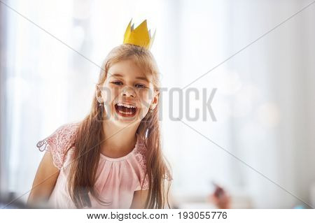 Cute little girl in a princess costume. Pretty child preparing for a party. Beautiful queen in gold crown.