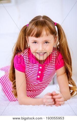 Joyful smiling child girl having a rest at home. Happy childhood.