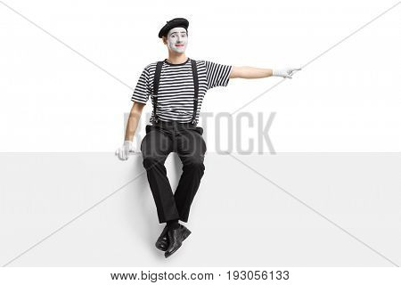 Mime sitting on a panel and pointing right isolated on white background