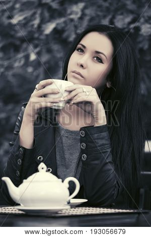 Young fashion woman drinking a tea at sidewalk cafe. Stylish female model in black leather jacket