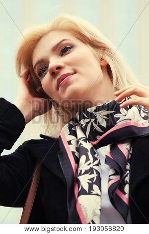 Happy fashion blond woman in black coat walking in city street