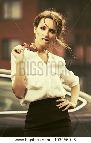 Young fashion business woman standing in a city street beside her car. Stylish female model in white blouse outdoor