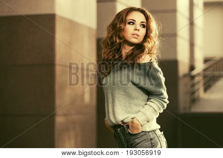 Happy young fashion woman in grey pullover walking in city street. Stylish female model with long curly hairs outdoor