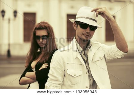 Young fashion couple walking in a city street. Stylish male and female model outdoor