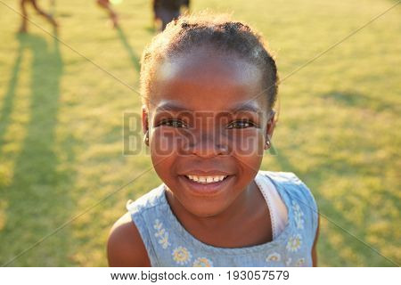 African elementary school girl smiling to camera outdoors